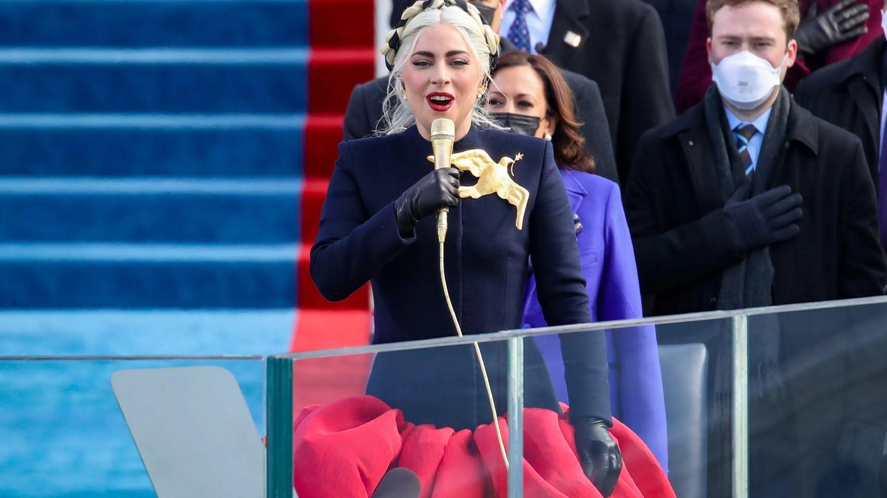 Lady Gaga mengenakan busana hitam merah, dengan pin burung emas di dadanya, pada pelantikkan Joe Biden.