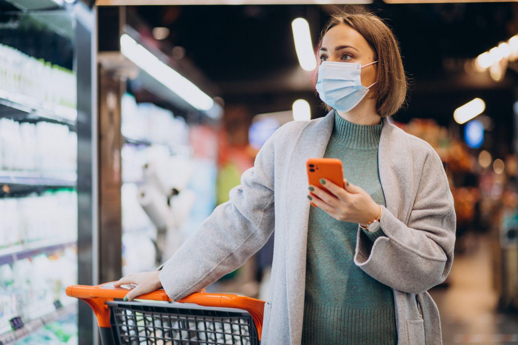 Update COVID-19 18/01/2021, rekor pasien sembuh terbanyak. Wanita menggunakan masker saat berbelanja.