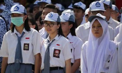 Siswi SMA Sedang berbaris mengenakan seragam putih abu dan topi